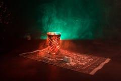 Östligt te i traditionell glasse och kruka på svart bakgrund med ljus och rök Östligt tebegrepp Armudu traditionella Azerb arkivfoto