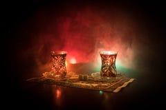Östligt te i traditionell glasse och kruka på svart bakgrund med ljus och rök Östligt tebegrepp Armudu traditionella Azerb royaltyfria foton