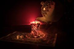 Östligt te i traditionell glasse och kruka på svart bakgrund med ljus och rök Östligt tebegrepp Armudu traditionella Azerb arkivbilder