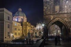 Östligt torn av Charles Bridge, korsfarare som är fyrkantiga i Prague arkivbild