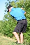 Öva den höga manliga golfaren för passform med Golf Club att svänga royaltyfria foton