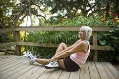 öva den mogna parken som sträcker kvinnan arkivfoton
