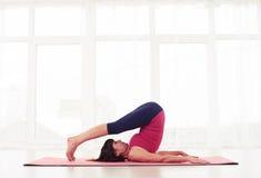 Öva den mogna yoginien för sportig passform yogahalasana, eller plogen poserar arkivfoto