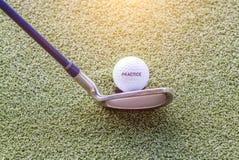 Öva golfboll och golfklubben på grön golfbana med varmt Royaltyfria Bilder
