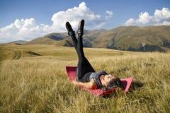 Öva konditionkvinnan som gör övningar i natur Flicka som gör M arkivfoto