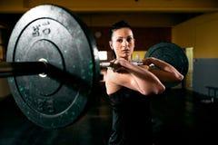 Öva med tungvikten, muskulös flicka som innehavet väger royaltyfri fotografi