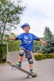 Övande balansera för lycklig pojke på en skateboard Royaltyfria Bilder