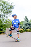 Övande balansera för lycklig pojke på en skateboard Fotografering för Bildbyråer