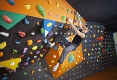 Övande bouldering för man i inomhus klättringidrottshall arkivfoto