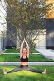 Övande yoga för attraktiv flicka utomhus arkivbild