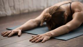 Övande yoga för attraktiv kvinna och att koppla av, når utbildning, liggande framsida ner arkivfoto