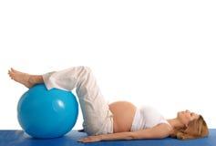 Övande yoga för gravid kvinna med den blåa bollen Arkivfoto