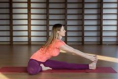 Övande yoga för härlig kvinna inomhus arkivbild