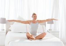 Övande yoga för härlig kvinna på henne underlag 库存照片