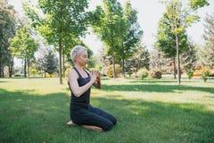 övande yoga för kvinna och framställningsgest med händer på gräs royaltyfria foton