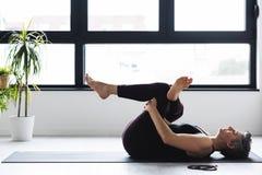 Övande yoga för mogen Caucasian kvinna på livingroomgolv royaltyfri fotografi