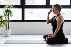 Övande yoga för mogen Caucasian kvinna på livingroomgolv arkivfoton