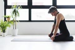 Övande yoga för mogen Caucasian kvinna på livingroomgolv royaltyfri bild