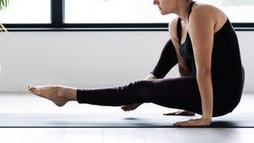 Övande yoga för mogen Caucasian kvinna på livingroomgolv fotografering för bildbyråer