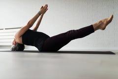 Övande yoga för mogen Caucasian kvinna på livingroomgolv arkivbild