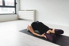 Övande yoga för mogen Caucasian kvinna på livingroomgolv royaltyfri foto