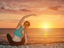 övande yoga för strandflicka Sikt från baksidan, solnedgång Arkivbild