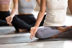 Övande yoga för svart kvinna och för grupp människor, halva Lotus arkivfoton