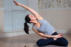 Övande yoga för ung attraktiv kvinna, sammanträde, bärande sportswear, meditationperiod royaltyfria foton