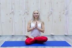 Övande yoga för ung attraktiv kvinna som sitter i den Padmasana övningen arkivbilder