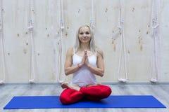 Övande yoga för ung attraktiv kvinna som sitter i den Padmasana övningen royaltyfri fotografi