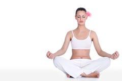 Övande yoga för ung kvinna i lotusblommapos. Royaltyfri Foto
