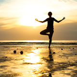 Övande yoga för ung kvinna på stranden på solnedgången Royaltyfria Bilder