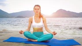 Övande yoga för ung kvinna på stranden på solnedgången Lotus poserar Royaltyfria Bilder