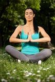 Övande yoga för ung kvinnlig i natur arkivfoto