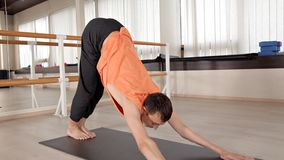 Övande yoga för ungt yogasportfolk som övar, sportar som beklär, begreppet av välbefinnande på yogastudion arkivfilmer