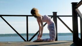 Övande yogadet fria för ung kvinna i sommar Sund livsstil arkivfilmer