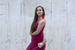 Övande yogavrikshasana för ung kvinna i idrottshall Isolerat på vit royaltyfri bild