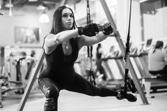 Övar idrotts- vägde utfall för kvinnagenomkörare ut squats för ändeben med upphängningremmar i konditionklubba eller idrottshall Arkivbild