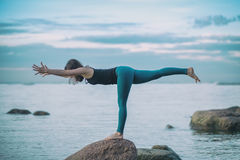 Övar praktiserande yoga för den unga attraktiva kvinnan som står i krigare tre, Virabhadrasana III poserar Arkivfoto