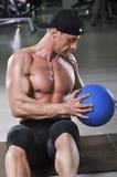 Övar utförande abs för stilig kraftig idrotts- man med medicinbollen Arkivfoto