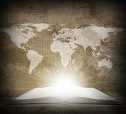 Över en öppen bok är en översikt av jorden Arkivbilder