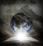 Över en öppen bok är planetjord Arkivbild