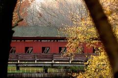 Över floden och till och med den röda dolda bron för trän fotografering för bildbyråer