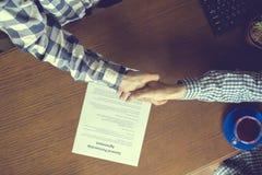 Över huvudet bästa sikt av två arbetare i tillfälligt i kontoret som undertecknar avtalsöverenskommelsen på tabellen arkivfoto