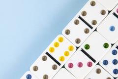 Över huvudet closeup av vita dominobrickor med ljust kulöra prickar på en blå bakgrund med kopieringsutrymme royaltyfria bilder