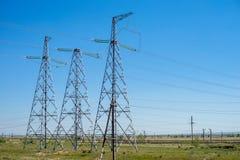 Över huvudet elektricitetsöverföringslinjer i sommaren, mot bakgrunden av den blåa himlen arkivfoto