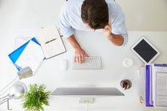 Över huvudet sikt av affärsmannen Working At Computer i regeringsställning Arkivfoton