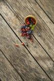 Över huvudet sikt av blandade bärfrukter som sprider ut ur träpilbåge Royaltyfri Foto