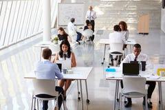 Över huvudet sikt av Businesspeople som i regeringsställning arbetar på skrivbord arkivfoto