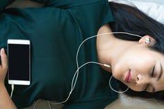 Över huvudet sikt av den härliga unga kvinnan som lägger ner på soffan genom att använda smartphonen för att lyssna musiken royaltyfria foton